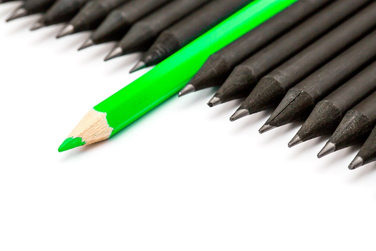 green pencil sticking out from black pencils